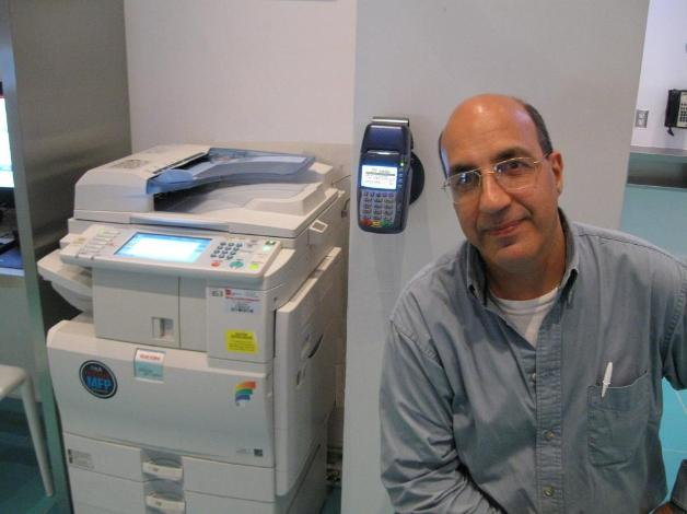 Basil Makhoul with a wall mounted CPI 420 series interfaced to a Ricoh MPC2551 at a Disney resort in Orlando for self service credit card payments of prints, copies and faxes